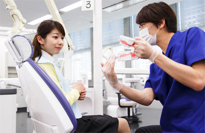 診療説明をする歯科医師と患者